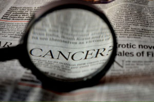 Cancer highlighted via magnifying glass