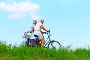 Two older persons on bicycles